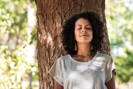 Peaceful woman leaning against a tree with her eyes closed