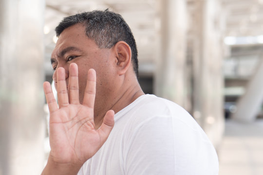 old man showing rejecting, stopping hand gesture; concept of forbidding, no way, rejection, negative answer, halt, stop, warning, social distancing; southeast asian senior old man model