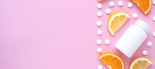 scattered vitamin pills and bottle with lemon orange on pink background. Copyspace, flat lay, banner. Concept boost immune system, medicine and tablets.
