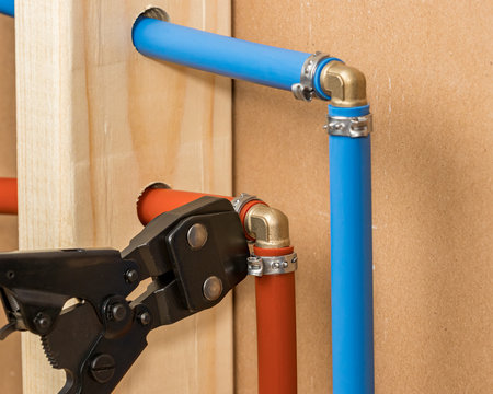 Pex plastic water supply plumbing pipe in wall of house. Concept of home repair, maintenance and remodeling