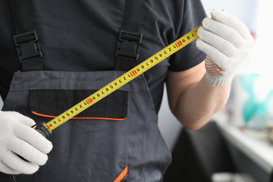 Repairman in uniform gloves measures tape measure. Choose right measuring tape. Marking and calculation area and required amount building materials. Repair and installation electrical wiring