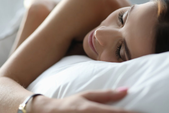 Young woman sleeping peacefully on white bedding. Sleep affects productivity. Physical forces are replenished. Girl adheres to sleep schedule. Bed is as comfortable as possible with hard base