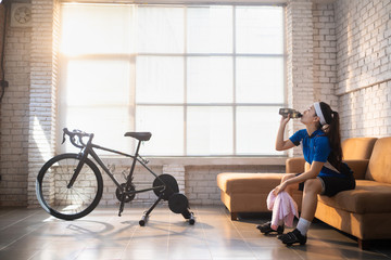 Asian woman cyclist. She is exercising in the house. By cycling on the trainer And play online bike games She breaks to drink water