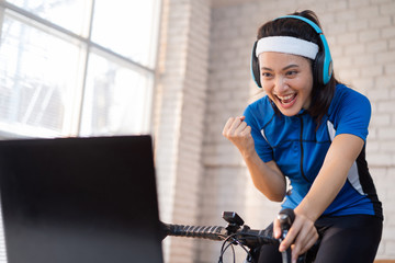 Asian woman cyclist. She is exercising in the house. By cycling on the trainer And playing online bike games, she is satisfied