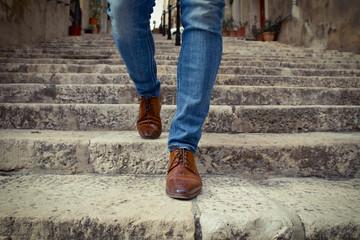 One men in brown shoes walking down outdoor stairway in city, detail of his legs