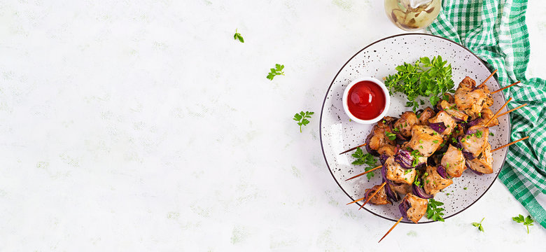 Grilled chicken kebab with red onions on a light table. Grilled meat skewers, shish kebab on light background. Top view, overhead, banner