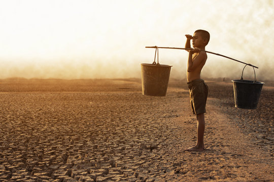 The boy sat on a parched ground due to water shortage due to global warming. Global warming and climate change concept