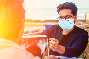 handsome indian man wearing mask and talking with worker colleague . corona virus epidemic and adaptation to new lifestyle