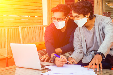 two handsome indian men wearing mask and talking with worker colleague . corona virus epidemic and adaptation to new lifestyle