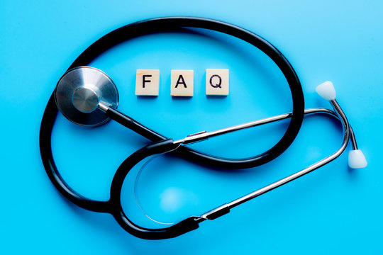 Wooden block form the word FAQ with stethoscope. Medical concept.