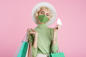 Spring online shopping during quarantine conception: fashionable woman wearing protective mask posing with colorful paper bags and plastic bank card. Pink background. Copy, empty space for text Fotobehang