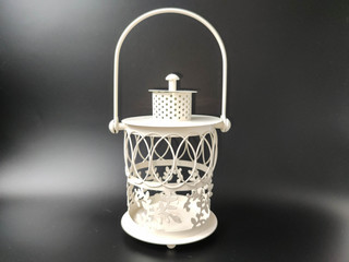 White vintage lantern with an orange candle on black. Concept - Ramadan kareem holiday celebration. Royalty Free Stock image