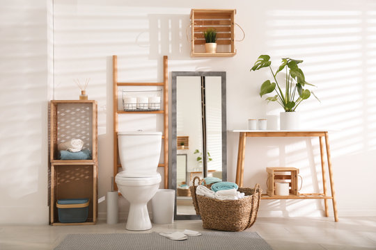 Interior of stylish bathroom with toilet bowl and decor elements