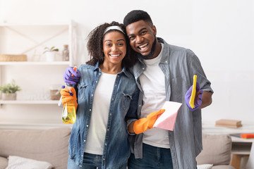 Black Couple Posing With Detergent Sprayers And Rags While Cleaning Apartment
