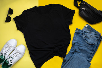 Black t-shirt mockup on yellow background. Flatlay with hipster clothes. Blue jeans, black sunglasses, white sneakers and shoulder bag