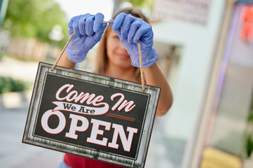 "Woman in blue gloves holding a nameplate ""we are open"", focus on nameplate"