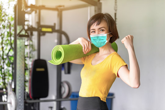 Young woman in sportswear doing work-out, sports training, gymnastics and wearing mouth mask against the corona virus. She's holding a training mat. Home fitness.