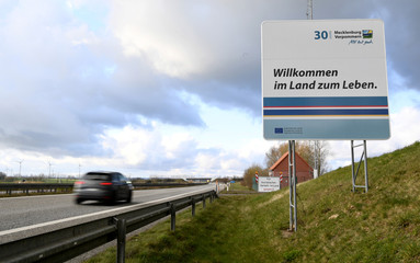 """Signs that read """"Welcome to the country to live"""" and """"Closed to tourist traffic in the state"""" are seen on the border of state Mecklenburg-Vorpommern"""