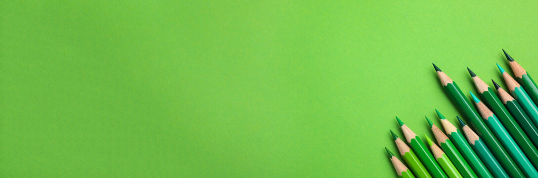 Color pencils on green background, flat lay with space for text. Banner design