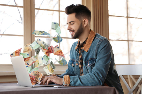 Man with modern laptop and flying euro banknotes at table indoors. People make money online