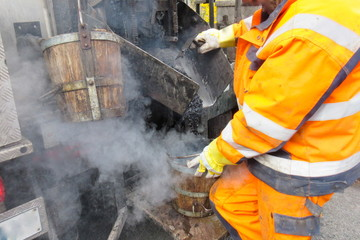 Road construction, road rehabilitation, asphalting. A worker in protective suit fills boiling hot asphalt from an asphalt machine into a bucket to fill a pothole.