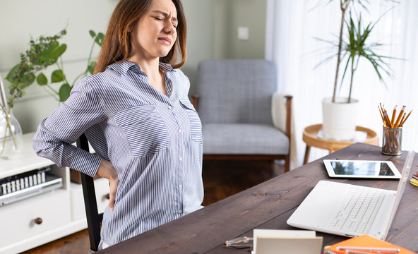 Freelancer young woman suffering with back pain