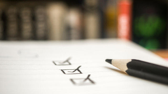 Black marking on checklist box with pencil close up book background Checklist concept