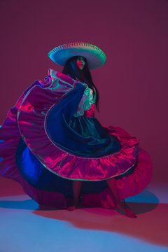 Fabulous Cinco de Mayo female dancer on purple studio background in neon light. Beautiful female model in traditional costume and sombrero dancing. Celebration, holiday, beauty and fashion concept.