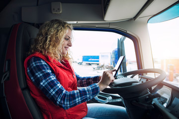 Truck driver setting up navigation GPS equipment to get directions for destination.