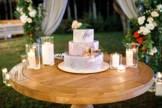 Beautiful delicious white wedding cake at the evening. Wedding cake for guests and brides