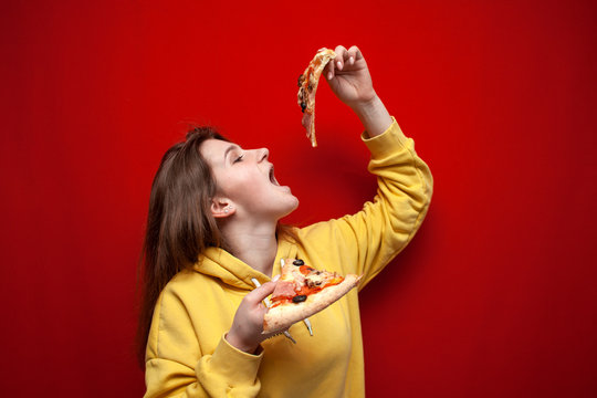 young happy girl eating pizza on a colored background, a teenager holds two slices of pizza and eat fast food