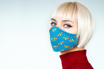 Woman wearing stylish handmade protective face mask. Fashion during quarantine of coronavirus outbreak. Copy, empty space for text Wall mural