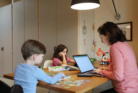 Eine Mutter arbeitet im Homeoffice zusammen mit ihren Kindern