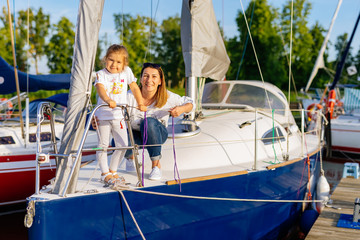 Portrait of smiling mother and daughter on prow of sailboat or yacht anchored in marina at bright sunny day. Blurred background with boats and trees