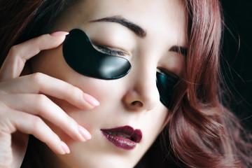 Foto op Plexiglas Beauty Woman with fashion dark makeup and black moisturizer under eyes hydrogel patches.