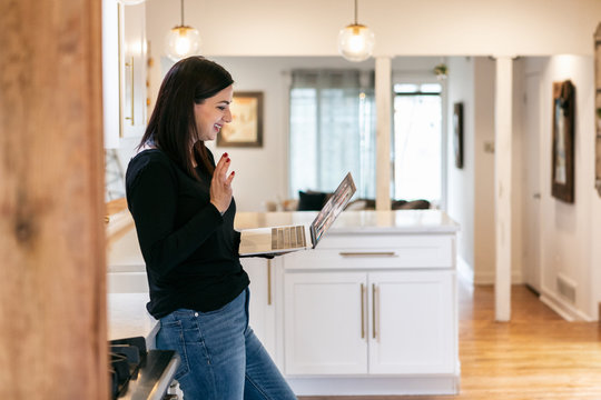 Staying Home: Woman Waves to Work Team On Laptop