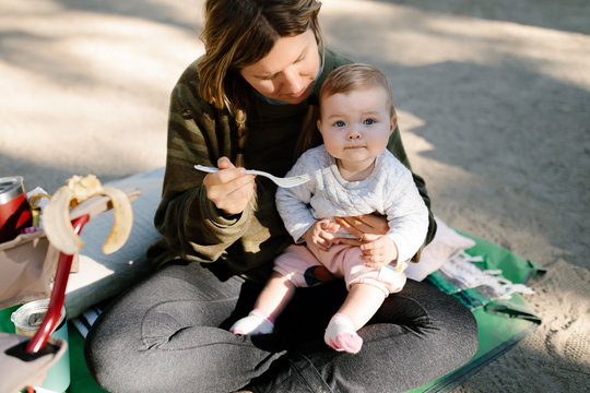 mother feeding her baby girl outdoors while camping