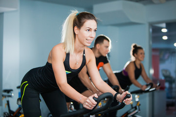 Cycling class in fitness club, group of fit people spinning on cardio machine