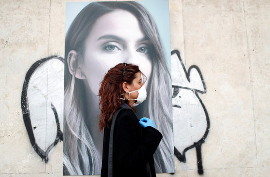 Italian chef Laura Carrera, 37, walks in order to go to the market wearing safe mask and gloves as the spread of coronavirus disease (COVID-19) continues, in Rome