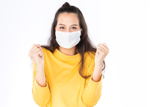 Young happy Asian woman wearing hygienic mask to prevent infection corona virus Air pollution pm2.5 she wearing a yellow sweater shoot in shot isolated on white background
