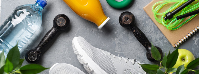 Healthy lifestyle concept. Health diary. Sneakers, water, dumbbells with a green apple on a gray background.