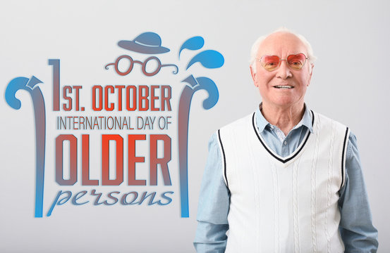 Portrait of happy elderly man on grey background. International day of older persons