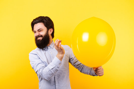 Man holding needle over yellow air balloon, a moment before bubble burst.