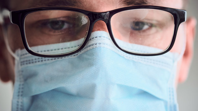 Close-up portrait of young sad and tired doctor in misted glasses and medical mask looking into camera