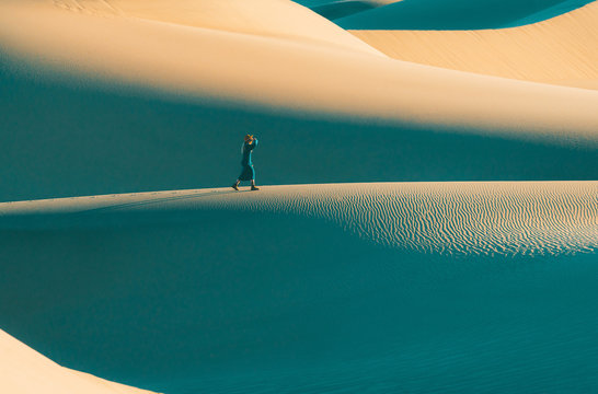 Woman walking on sand dunes