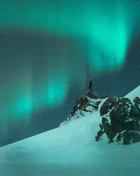 Man standing on rock under Aurora Borealis