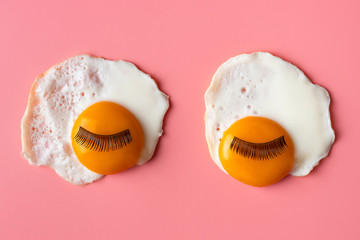 Pop art background. fried eggs with eyelashes on a pinkbackground. Food art. Morning concept. looks...
