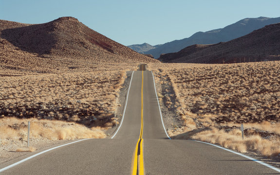 Lonely road in the Mojave desert in California. The hill on the left is of volcanic origin.