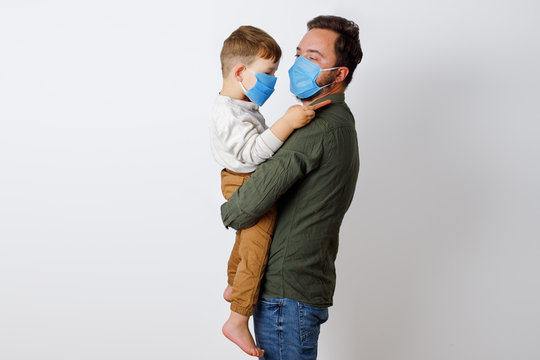 young father and his toddler son wearing surgical masks on a white background.