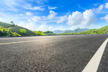 Empty asphalt road and green tea plantation nature landscape.